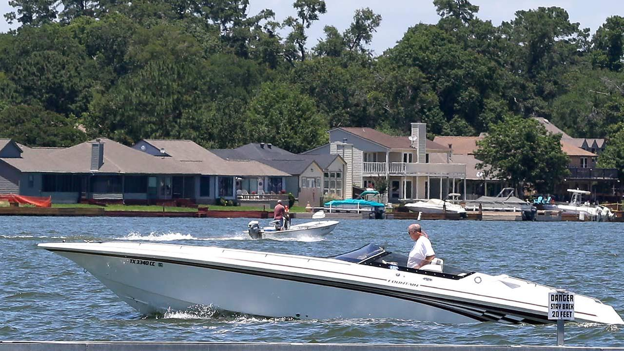 In this Tuesday, June 10, 2014 photo, pleasure boats cut through the waters of Lake Conroe, near Conroe, Texas.