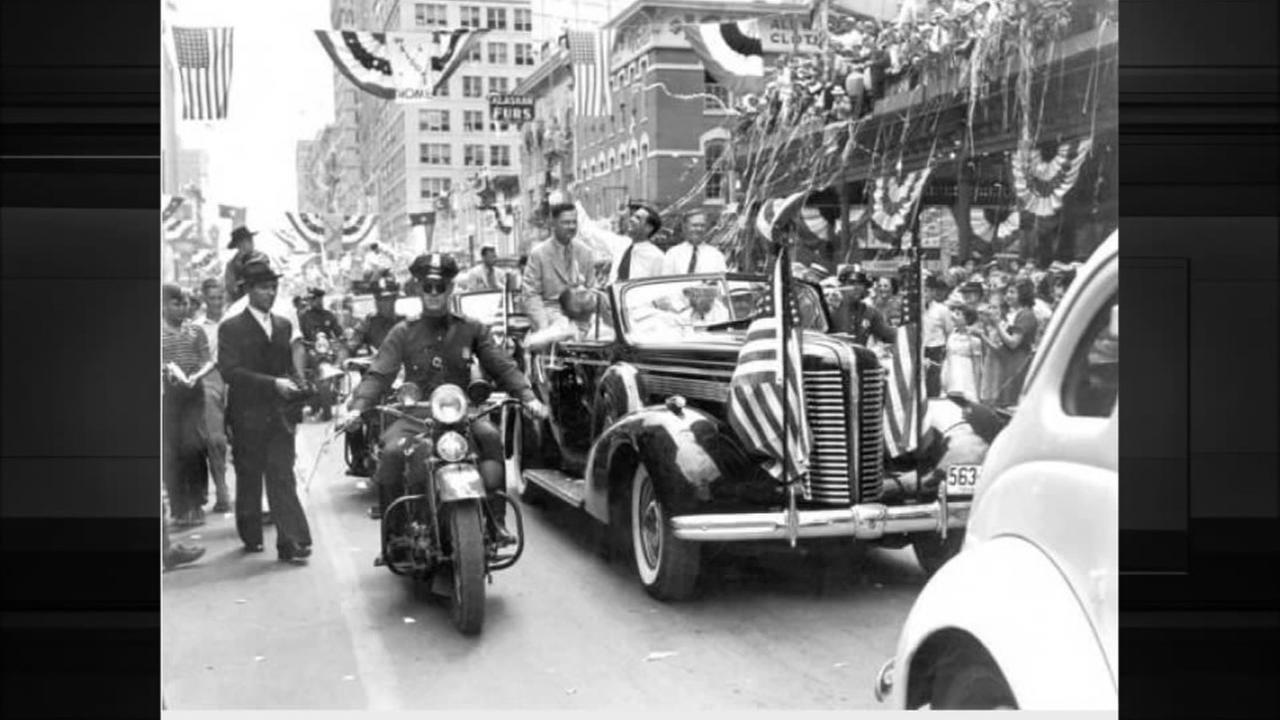 Howard Hughes in open car with Mayor Fonville taken from street level. Motorcycle outriders. Crowd in front of Rice Hotel in background.  Photo: Houston Public Library-HMRC
