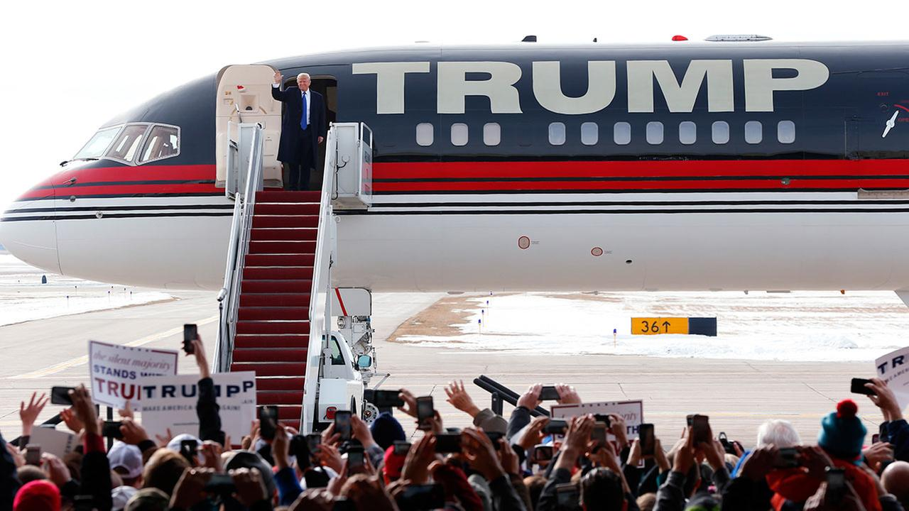 Republican presidential candidate Donald Trump waves as he arrives on his plane at a campaign event at Dubuque Regional Airport, Saturday, Jan. 30, 2016 in Dubuque, Iowa.