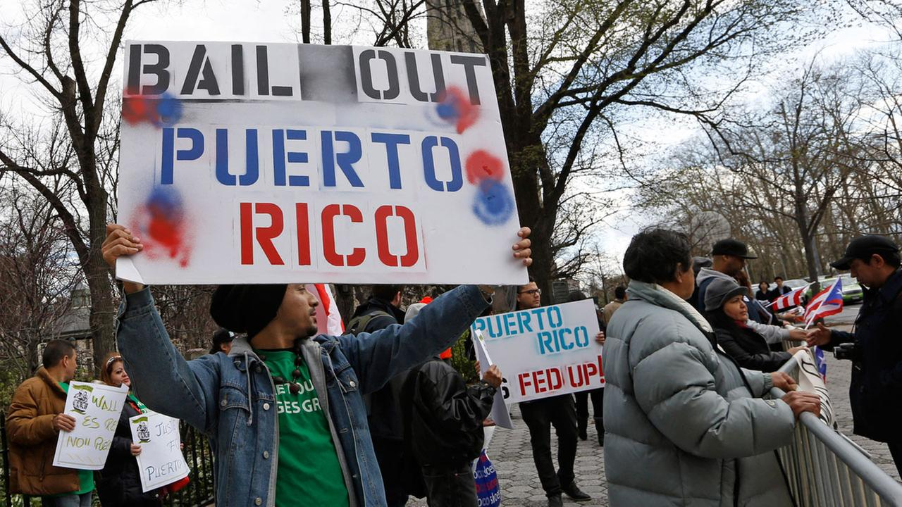 A demonstrator protests the Federal Reserves failure to bail out Puerto Rico outside International House, Thursday, April 7, 2016, in New York.