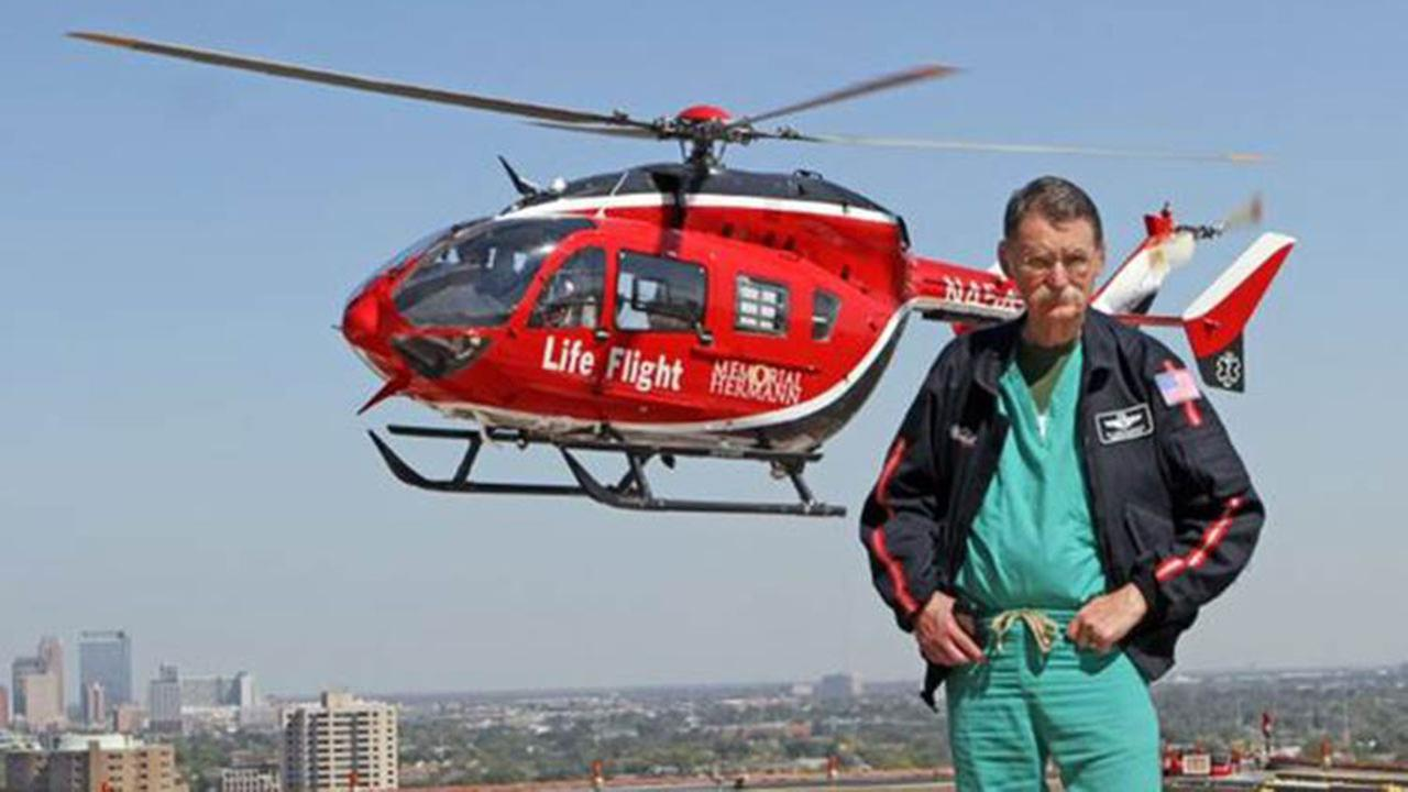 Dr. James H. Red Duke poses in front of a Life Flight helicopter.
