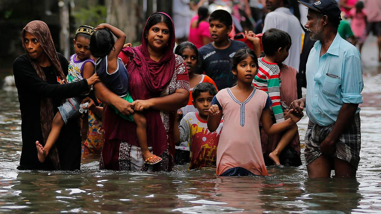 Sri Lankans wade through a road submerged in flood waters in Colombo, Sri Lanka, Tuesday, May 17, 2016. The Disaster Management Center said that 114 homes have been destroyed and m