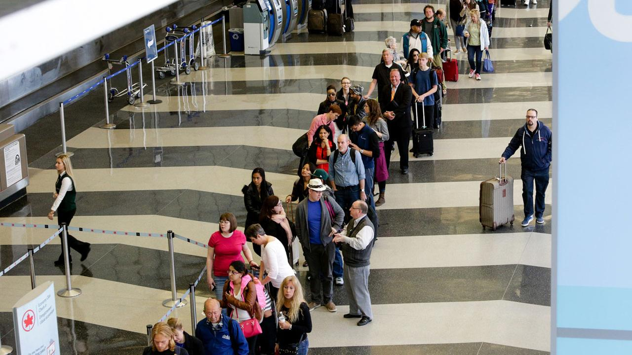 A long line of travelers wait for the TSA security check point at OHare International airport, Monday, May 16, 2016, in Chicago.