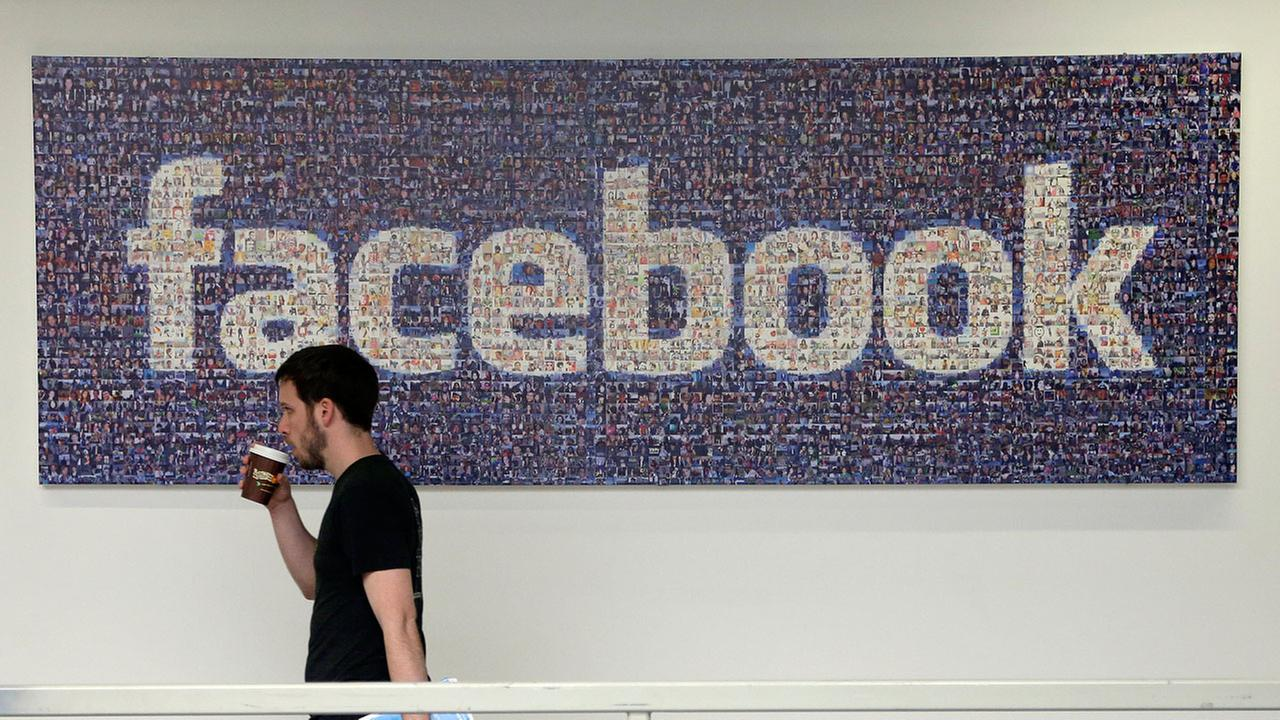 A Facebook employee walks past a sign at Facebook headquarters in Menlo Park, California.