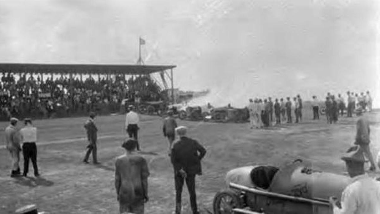 Crowded grandstand filled with people watching the start of a race at Bellaire (Tex.). Idle racecars at lower portion of photograph.