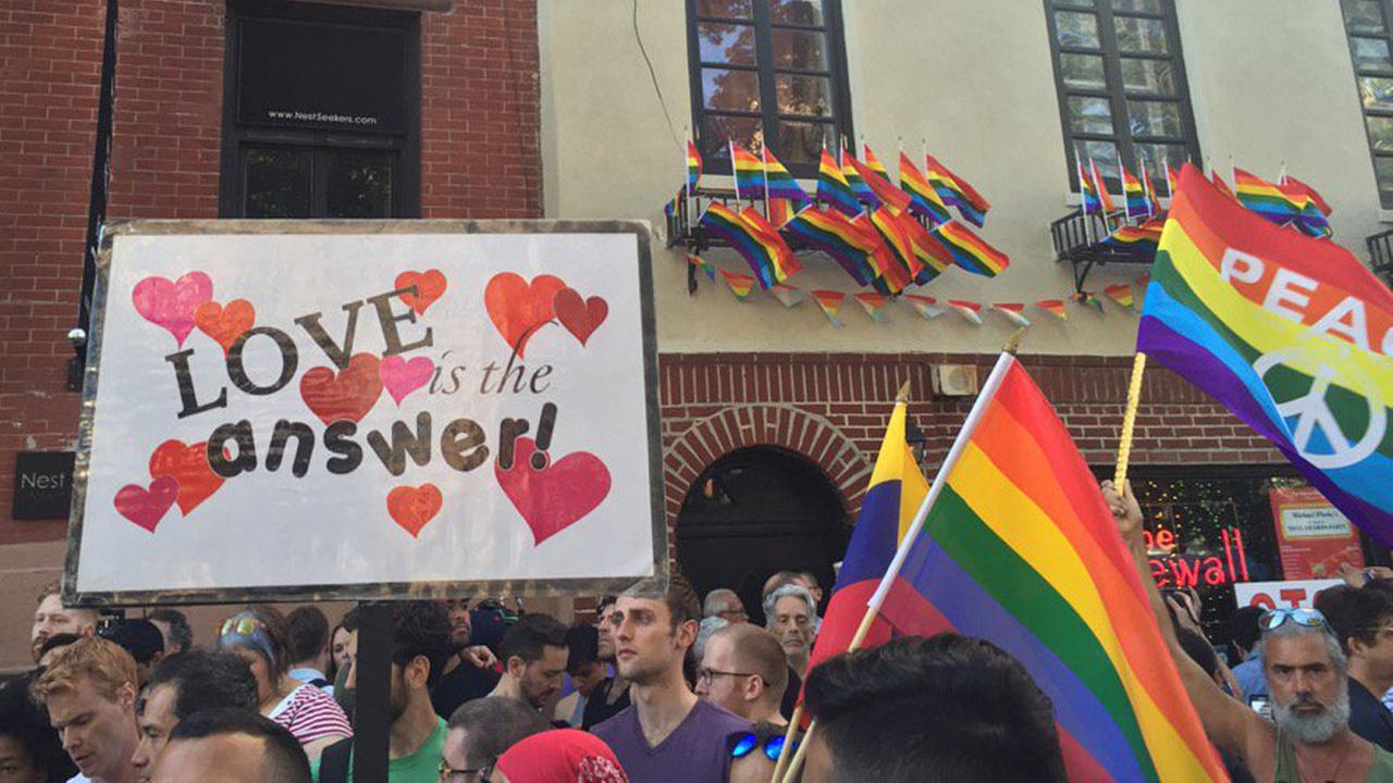 Demonstrators march with signs and LGBT Pride flags during an event in New York City. @louisxharrry/Twitter