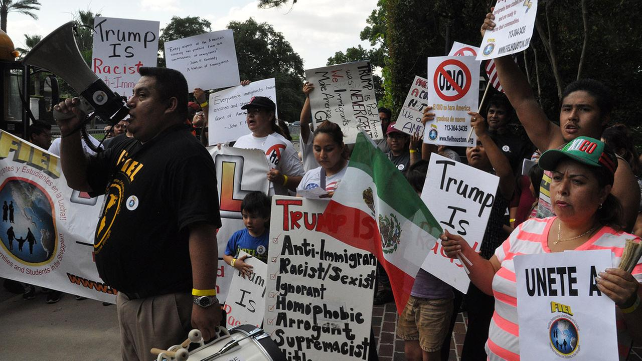 Protesters gather across the street from the site of a Donald Trump fundraiser in River Oaks Friday.