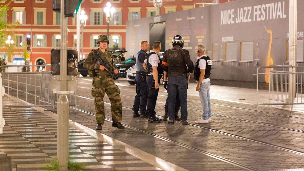 Police officers and a soldier stand by the sealed off area of an attack after a truck plowed through a crowd of revelers in Nice, France.AP Photo/Ciaran Fahey
