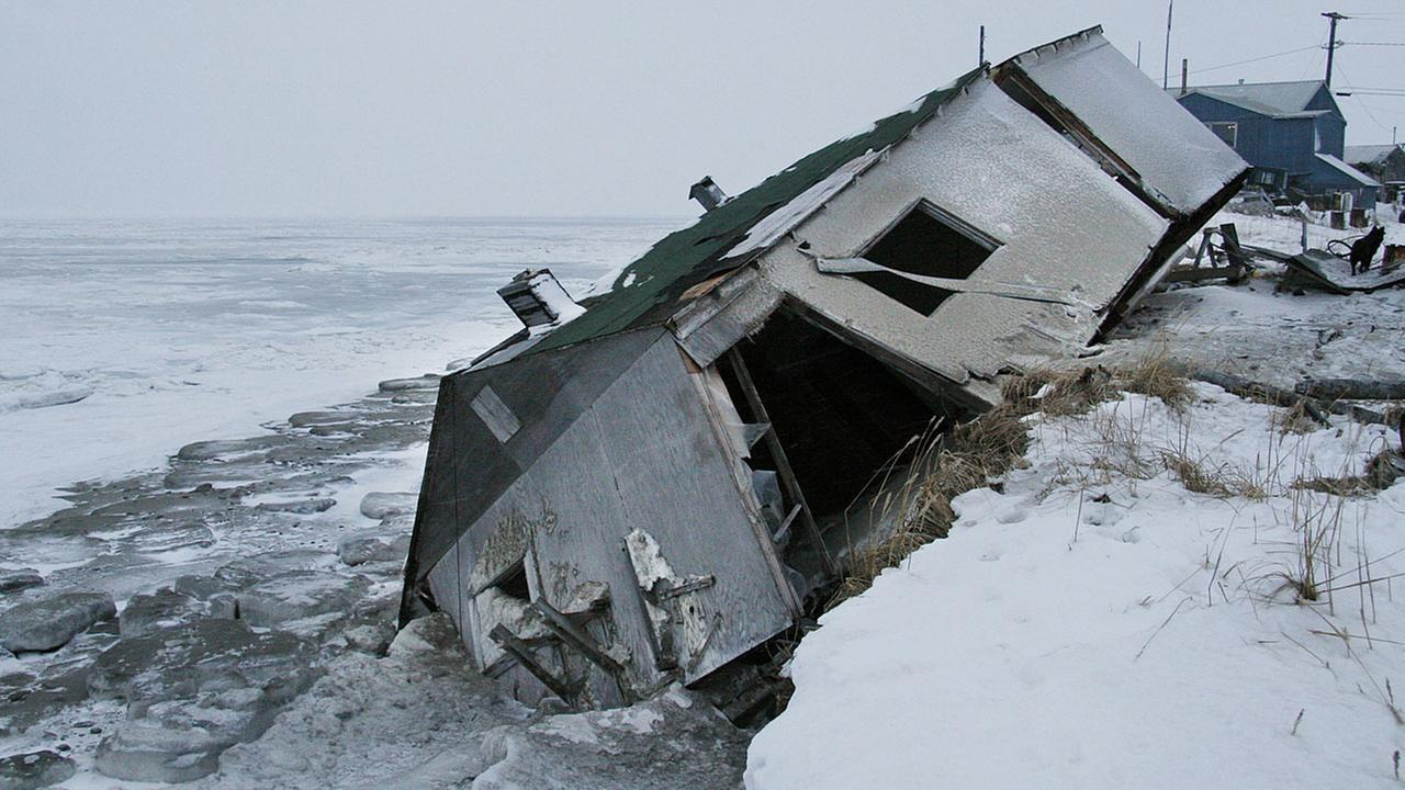 Nathan Weyiouannas abandoned house at the west end of Shishmaref, Alaska, Dec. 8, 2006, sits on the beach after sliding off during a fall storm in 2005.