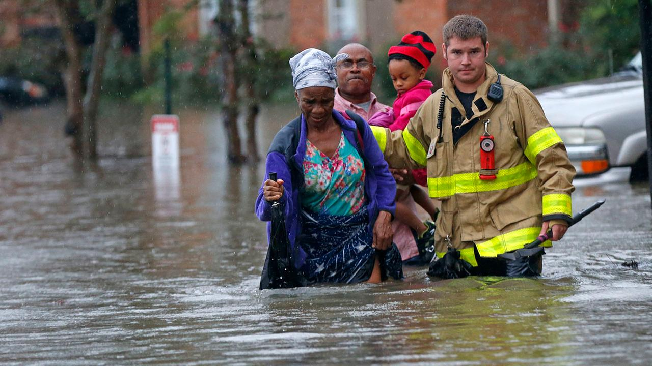 A member of the St. George Fire Department assists residents as they wade through floodwaters from heavy rains in the Chateau Wein Apartments in Baton Rouge, La.