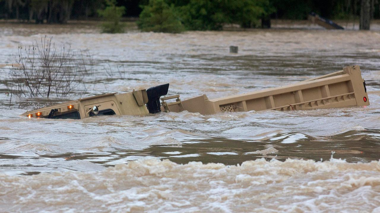 In this Sunday, Aug. 14, 2016 photo, a Louisiana Army National Guard dump truck that drove off the road is submerged in flood waters near Walker, Louisiana.