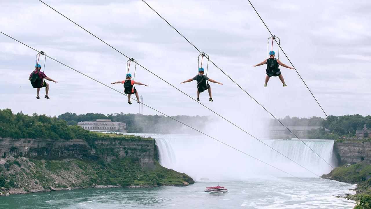 In this July 19, 2016 photo, tourists suspended above the water from zip lines make their way at speeds of up to 40 mph toward the the mist of the Horseshoe Falls.