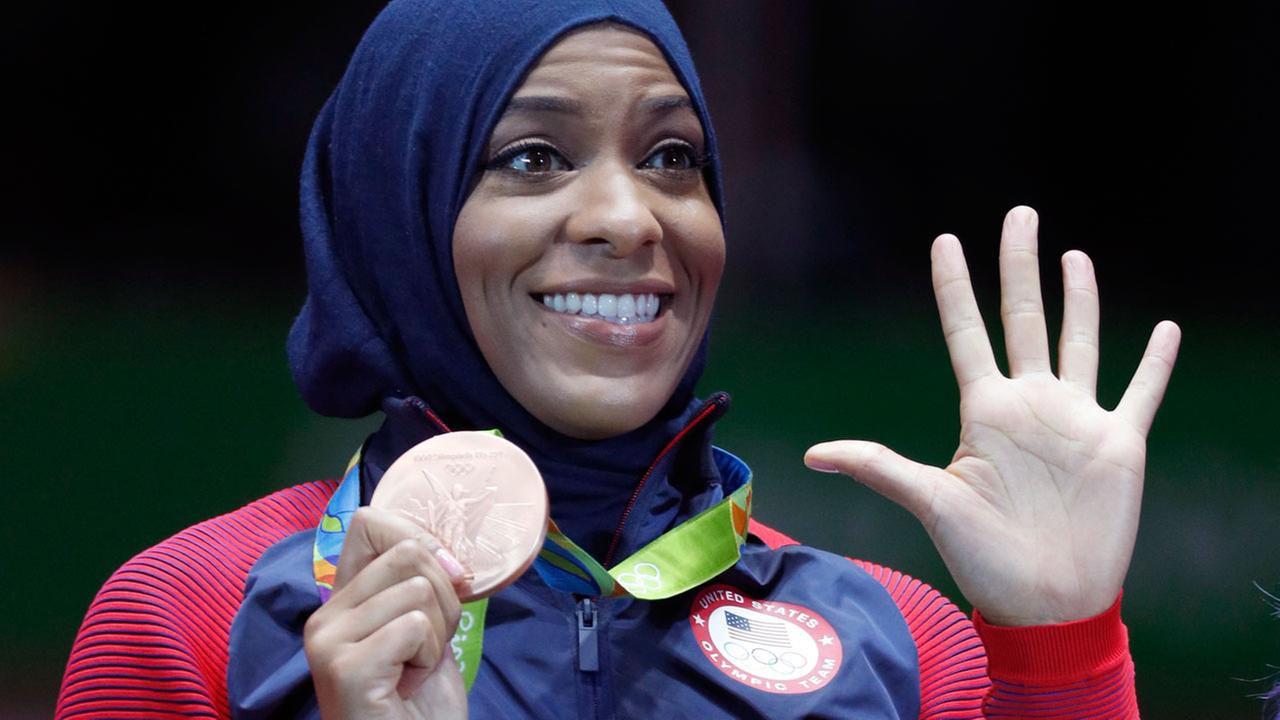 Ibtihaj Muhammad of the United States pose with her bronze medals on the podium after the womens team sabre fencing event at the 2016 Summer Olympics in Rio de Janeiro.