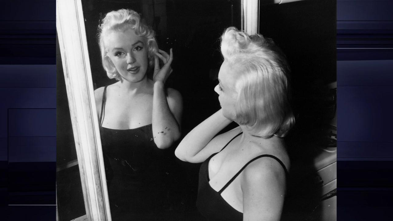 Actress Marilyn Monroe, film star turned business executive, checks her lines - all curves - in a mirror at the photographic studio of her business partner, Milton Greene