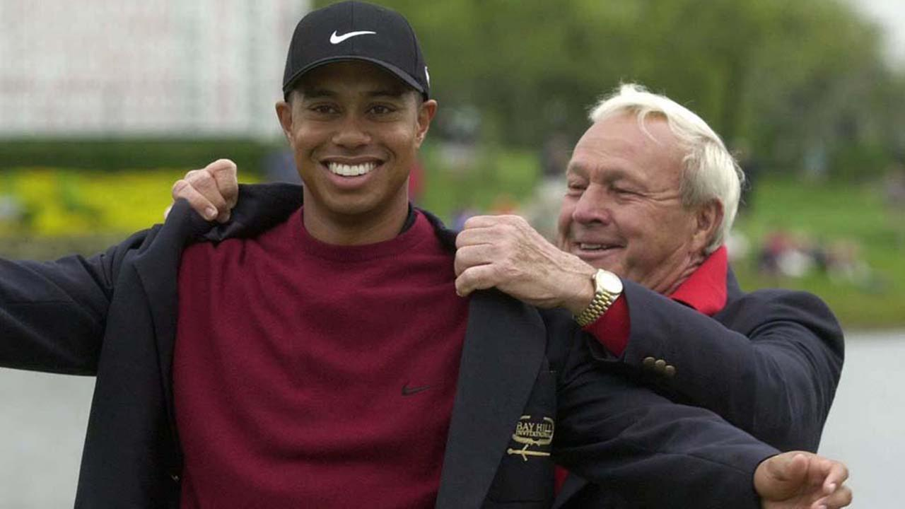 Tiger Woods, left, is helped into the his jacket for winning the Bay Hill Invitational by tournament host Arnold Palmer on Sunday, March 18, 2001.ASSOCIATED PRESS