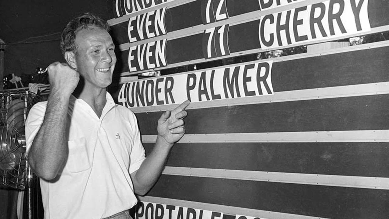 A June 19, 1960, file photo shows Arnold Palmer pointing to his name on a scoreboard showing his four-under-par total, for 72 holes, during the National Open in Colorado.AP
