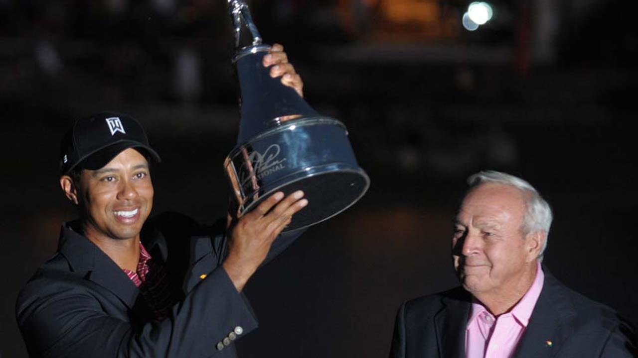 Tiger Woods, left, lifts the trophy for winning the Arnold Palmer Invitational golf tournament as Arnold Palmer looks on in Orlando, Fla., Sunday, March 29, 2009.ASSOCIATED PRESS