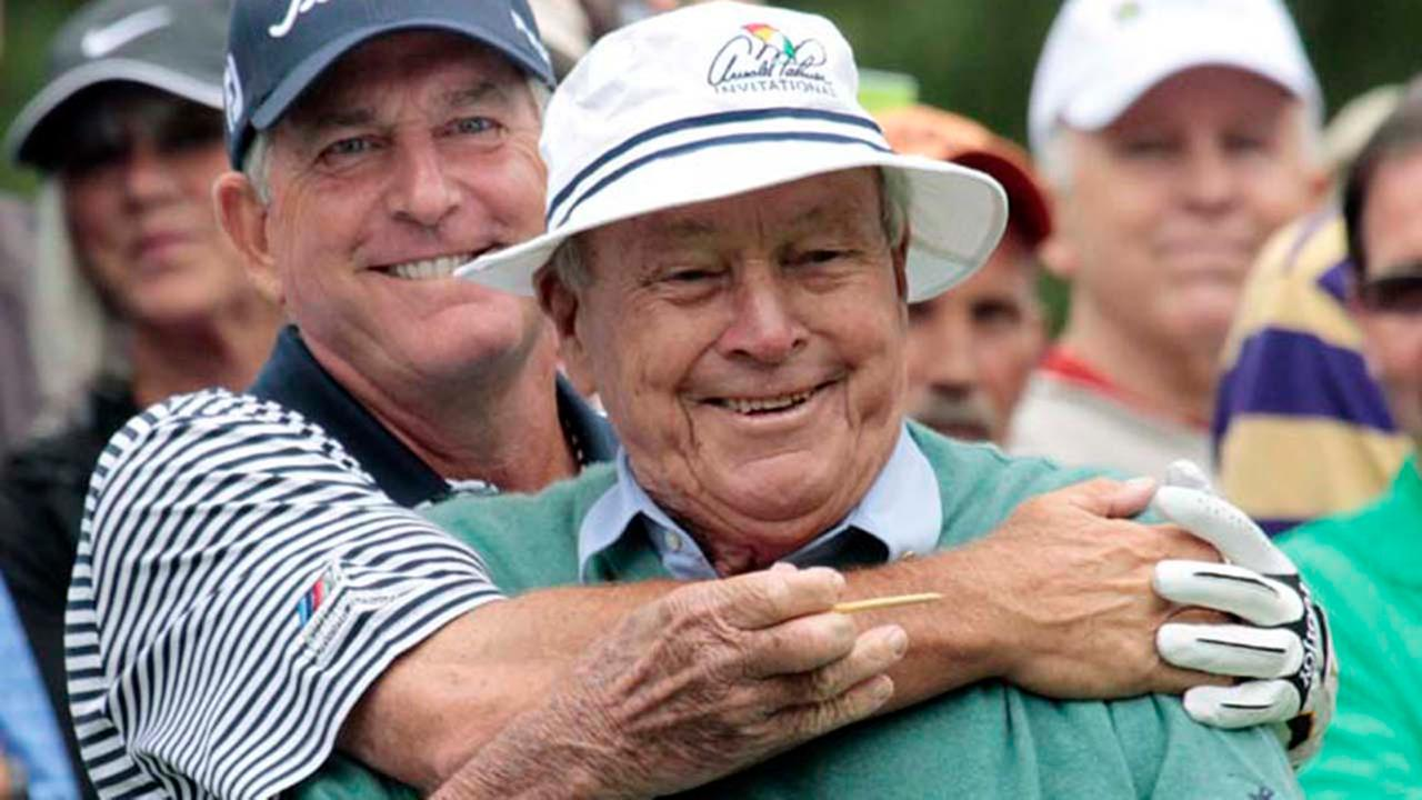Jay Haas, left, gives Arnold Palmer a hug from behind before teeing off for the Umpqua Challenge golf tournament in Portland, Ore., Monday, Aug. 29, 2011.AP
