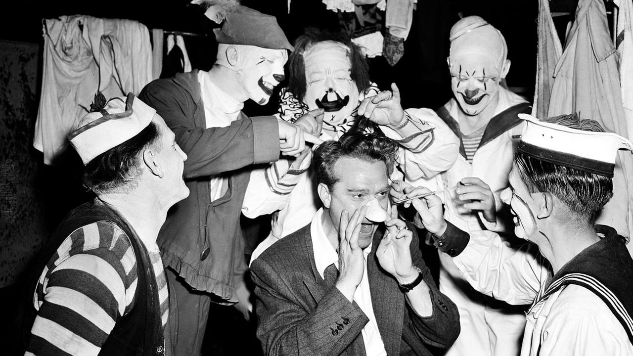 Comedian Red Skelton is surrounded by clowns of the Clyde Beatty Circus, giving him a helping hand as he puts on a big nose, in Los Angeles, Calif., in June 1946.AP Photo