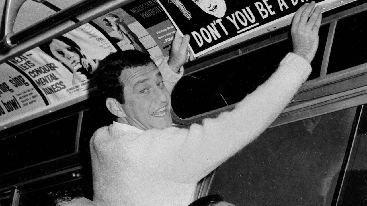 Comedian Soupy Sales demonstrates his serious side by installing a placard in a bus urging teenagers to stay in school, Sept. 25, 1962, in Los Angeles.AP Photo