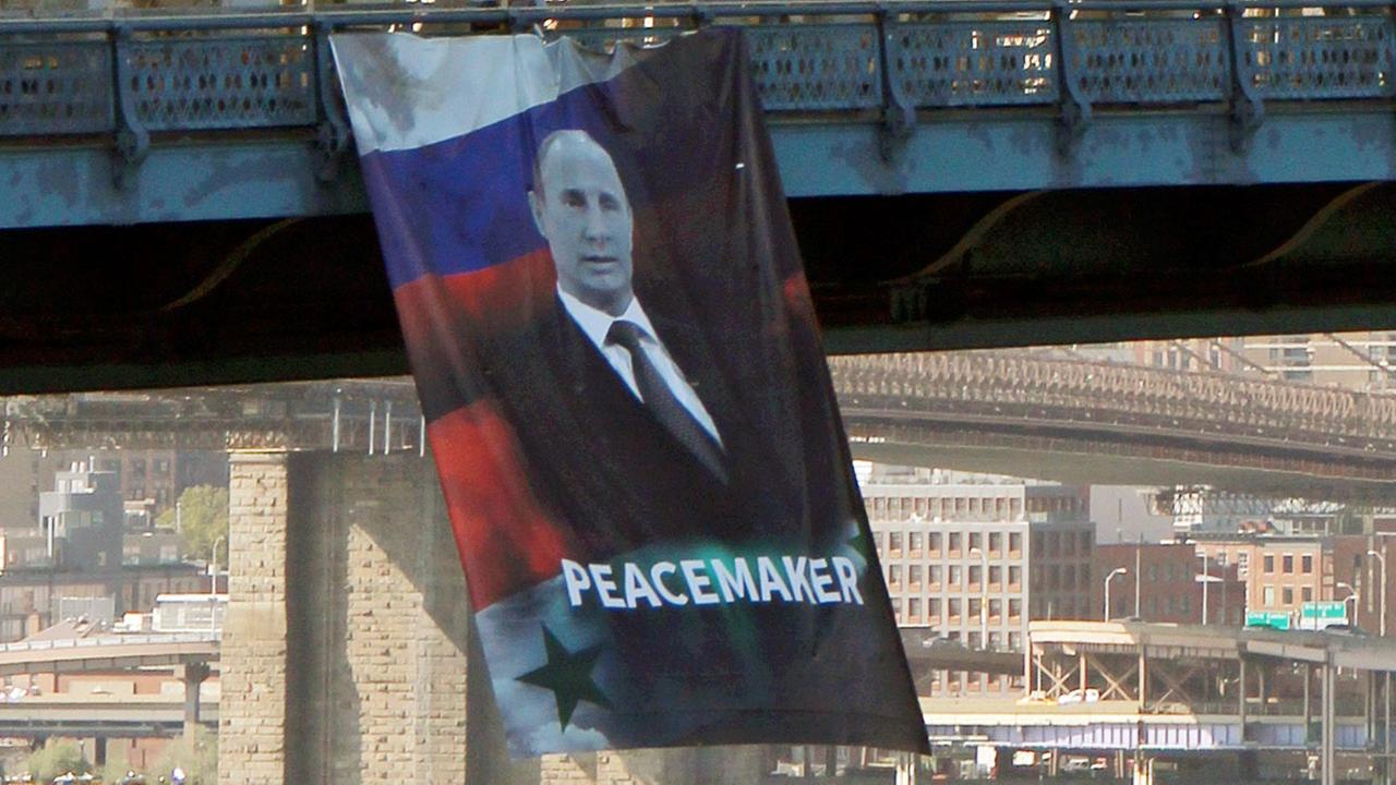 A banner bearing an image of Russian President Vladimir Putin showing him with a Russian and Syrian flag as backdrop and labeling him a peacemaker hangs from the Manhattan Bridge
