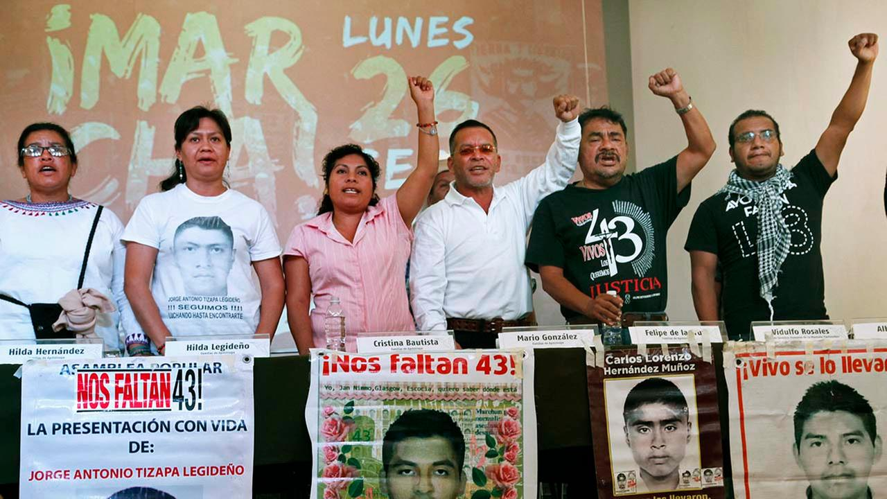 Relatives of 43 missing students from the Isidro Burgos Rural Normal School of Ayotzinapa hold up their fists behind photos of their missing family members