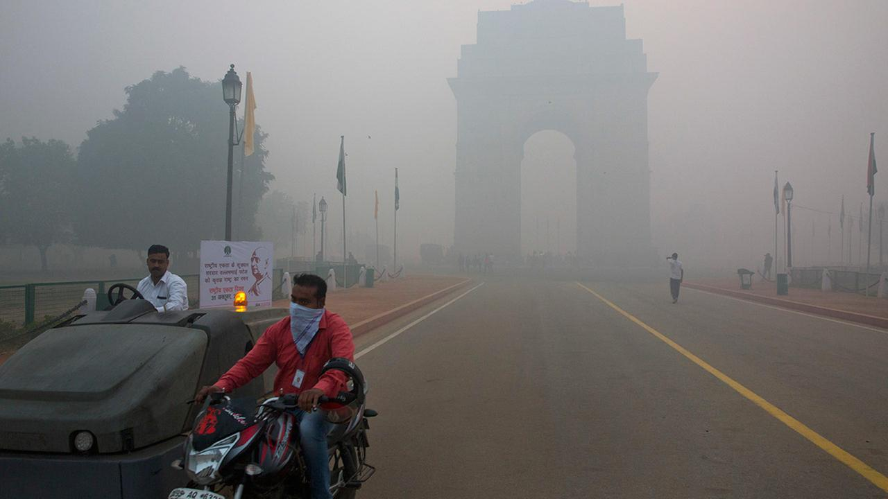 In this Monday, Oct. 31, 2016 photo, a man covers his face with a scarf as he rides in front of the landmark India Gate, enveloped by smoke and smog, in New Delhi, India.