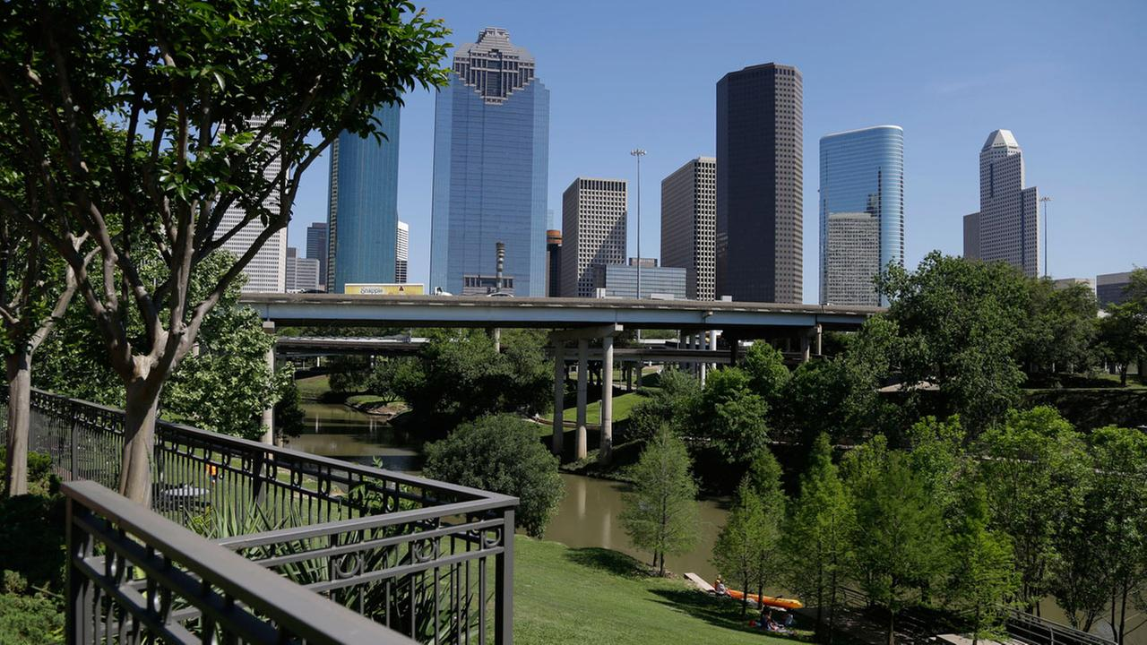 A railing from an apartment complex and the Houston skyline overlook the Buffalo Bayou as it snakes its way into downtown Friday, April 18, 2014.