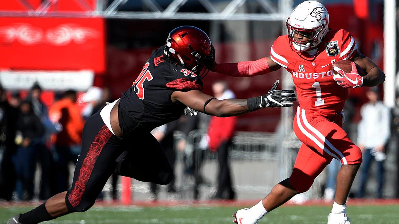 Houston quarterback Greg Ward Jr. (1) avoids a tackle from San Diego State defensive lineman Noble Hall during the first half of the Las Vegas Bowl. (AP Photo/David Becker)