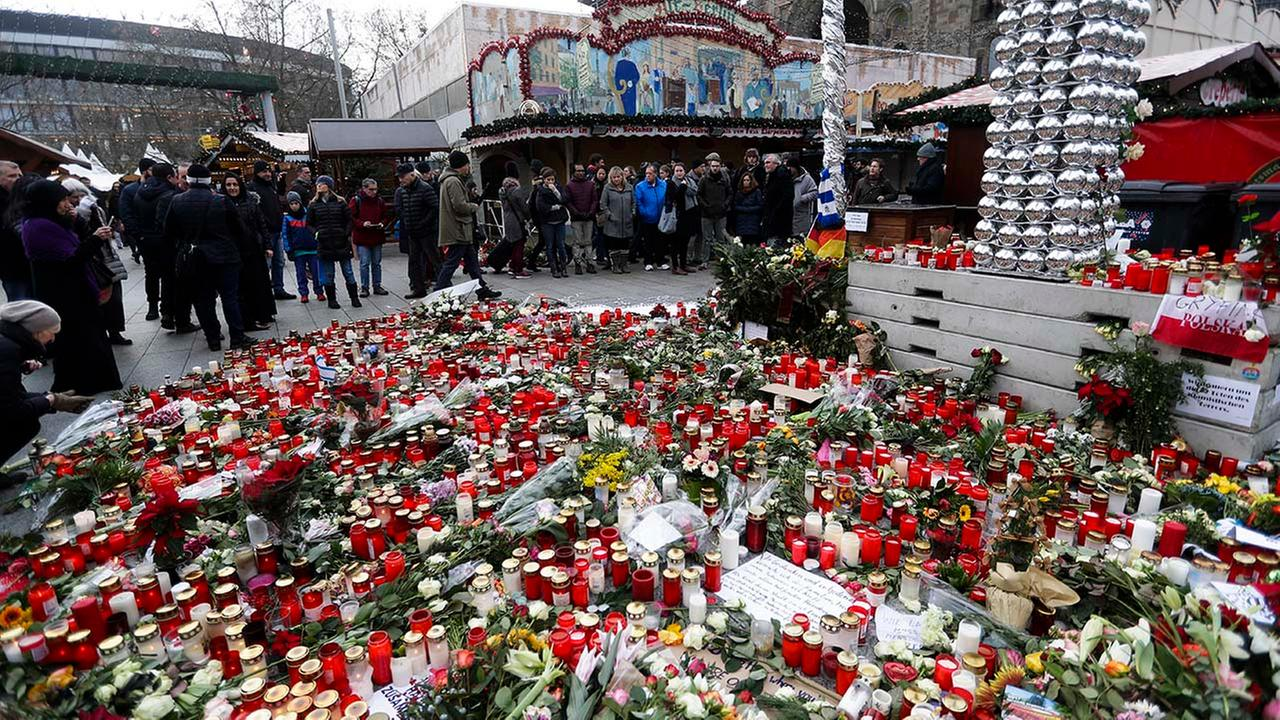 People stand around candles at the reopened Christmas market, three days after a truck ran into the crowd and killed several people, at the Kaiser Wilhelm Memorial Church in Berlin