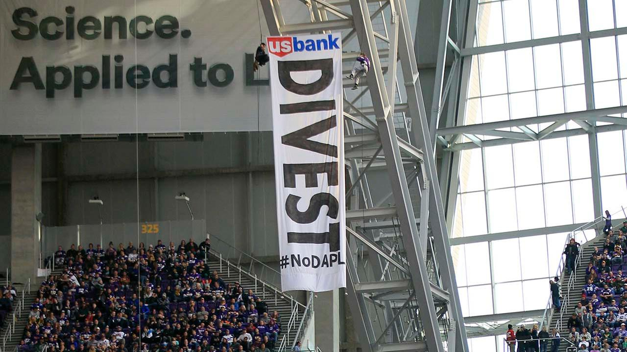 Protesters against the Dakota Access Pipeline rappel from the catwalk in U.S. Bank Stadium during the first half of an NFL football game.AP