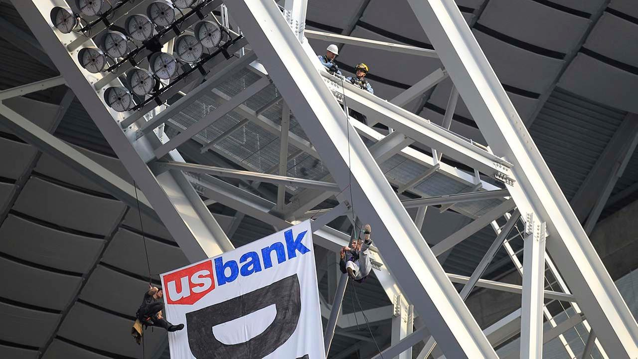 Officials talk with protesters opposed to the Dakota Access Pipeline after they rappelled from the catwalk in U.S. Bank Stadium during the first half of an NFL football game.AP