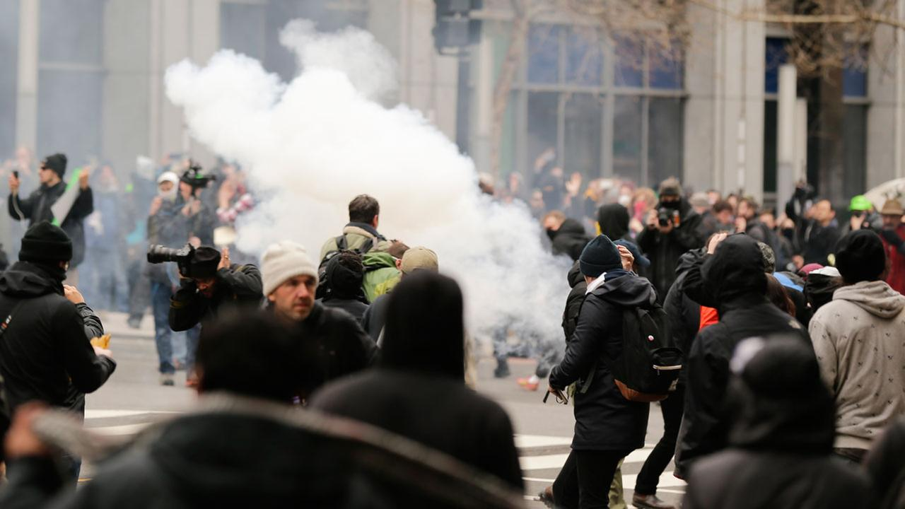 Police deploy smoke and pepper grenades during clashes with protesters in northwest Washington, Friday, Jan. 20, 2017.