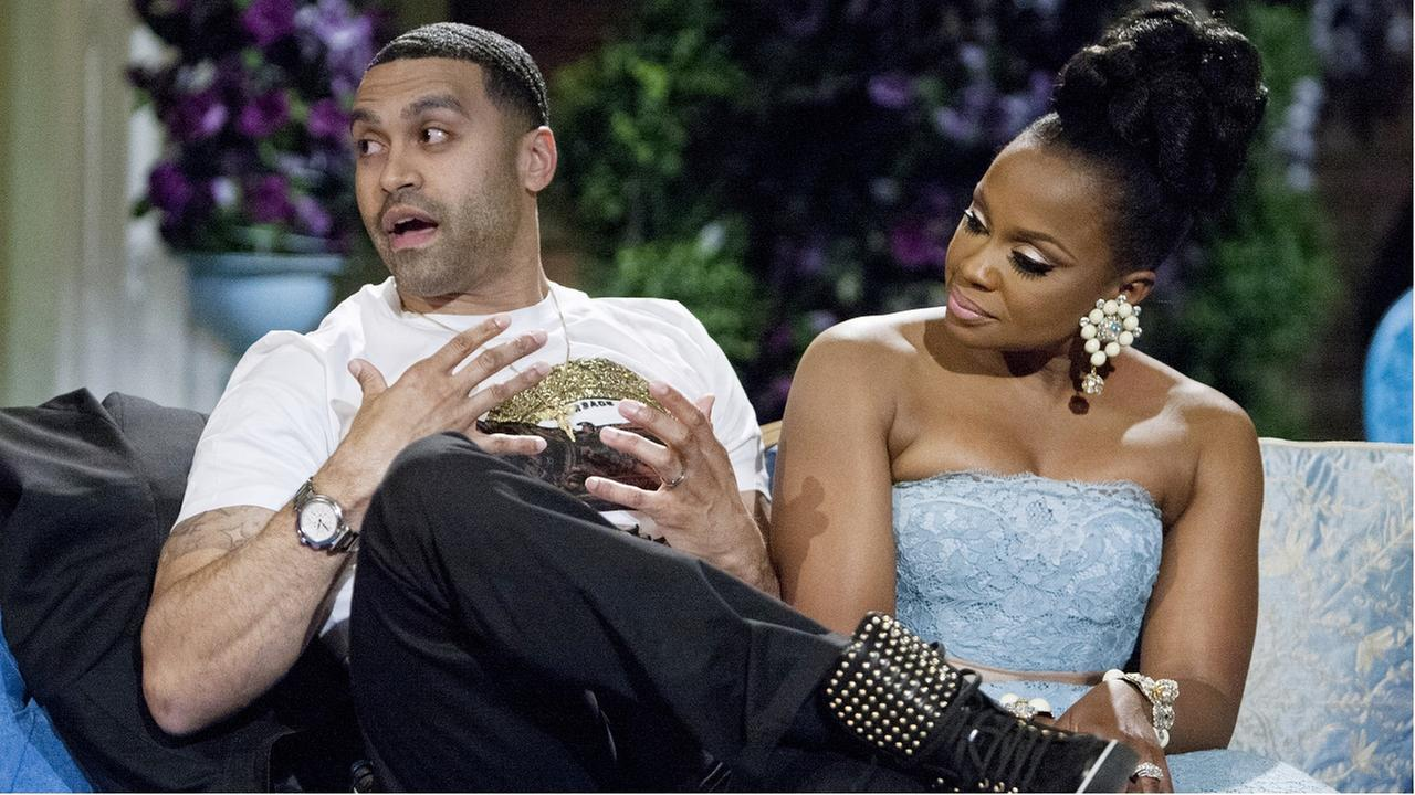 This 2014 image released by Bravo shows Apollo Nida, left, and his wife Phaedra Parks, cast members on The Real Housewives of Atlanta, during the taping of a reunion special.