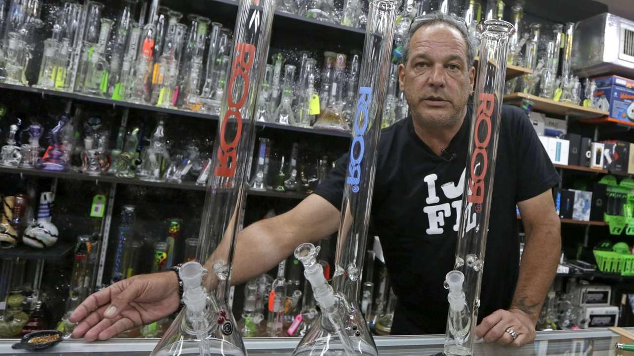 Jay Work talks to a reporter as he places tobacco on the counter next to three authentic Roor water pipes, at his Grateful Js smoke shop Thursday, Jan. 12, 2017, in Margate, Fla.AP