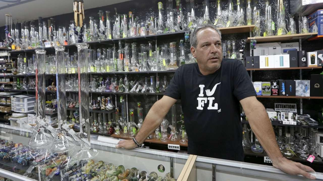 Jay Work talks to a reporter at his Grateful Js smoke shop, on the counter on the left, are three authentic Roor water pipes, Thursday, Jan. 12, 2017, in Margate, Fla.AP