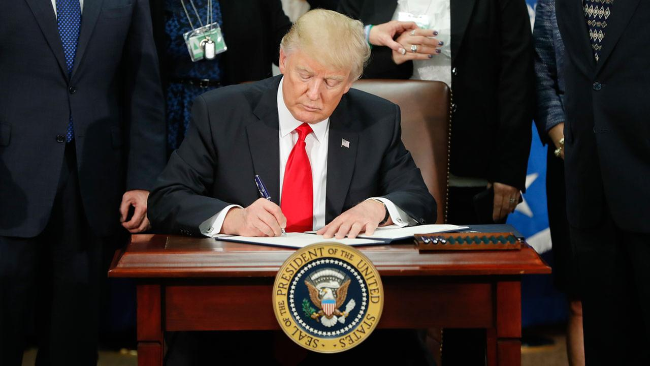President Donald Trump signs an executive order for border security and immigration enforcement improvements, Wednesday, Jan. 25, 2017, at the Homeland Security Department.