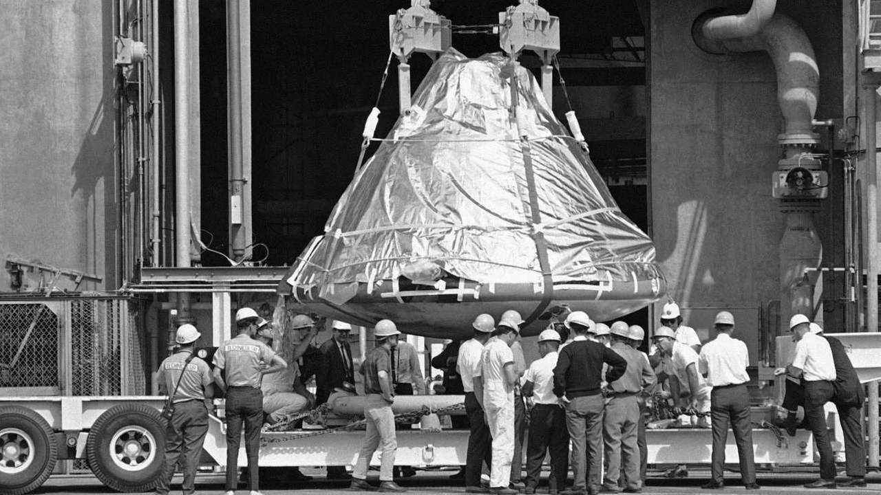 In this Feb. 17, 1967 file photo, technicians and officials inspect the aluminum covered Apollo 1 spacecraft after it was lowered from its booster at pad 34 at Cape Kennedy, Fla.AP