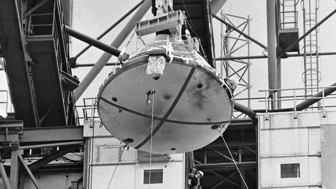 FILE - In this Feb. 17, 1967 file photo, the Apollo 1 capsule, with black smudge marks visible on the heat shield, is lowered from its Saturn 1 booster at Cape Kennedy, Fla.AP