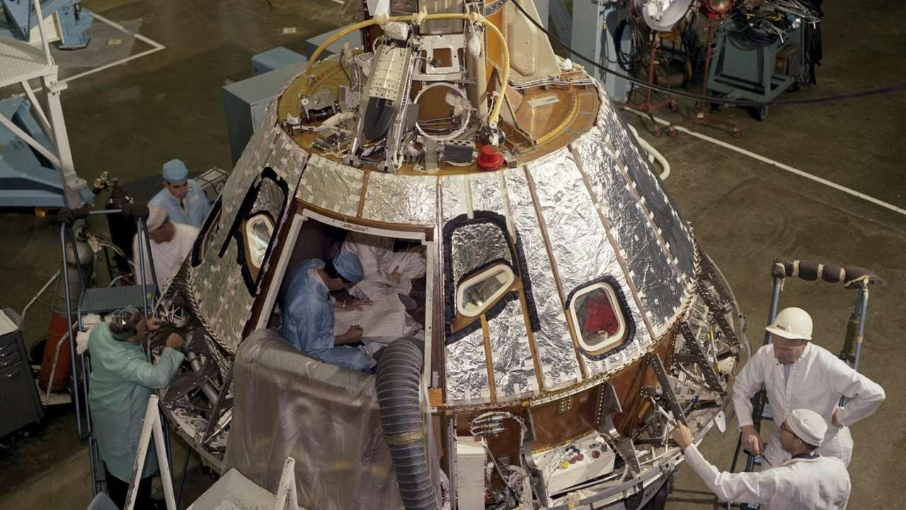 In this 1966 photo made available by NASA, technicians work on the Spacecraft 012 Command Module at Cape Kennedy, Fla., for the Apollo/Saturn 204 mission.AP