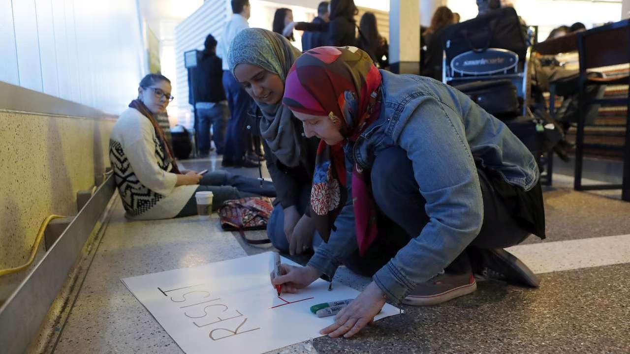 Pamela Thompson, right, and Irfana Hasmi, center, make signs as protests against President Donald Trumps executive order banning travel from seven Muslim-majority countriesAP