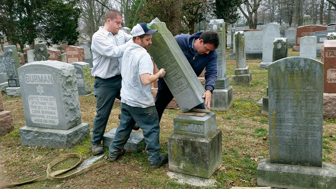Nathan Fohne, Derek Doolin and Philip Weiss hoist a headstone at the Chesed Shel Emeth Cemetery, where over 150 headstones had been tipped over.