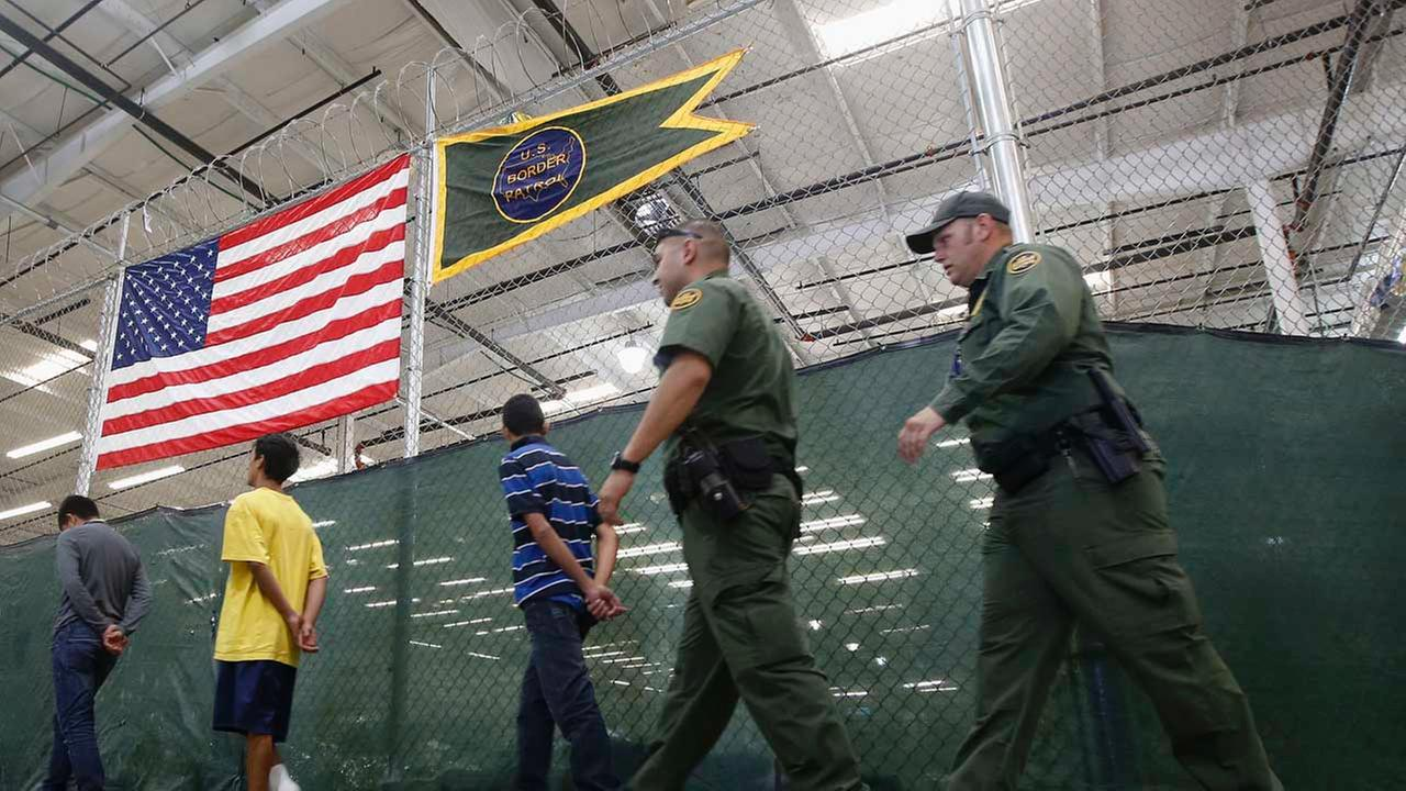 Young detainees being escorted to an area to make phone calls as hundreds of mostly Central American immigrant children are being processed and held at the U.S. Customs and Border