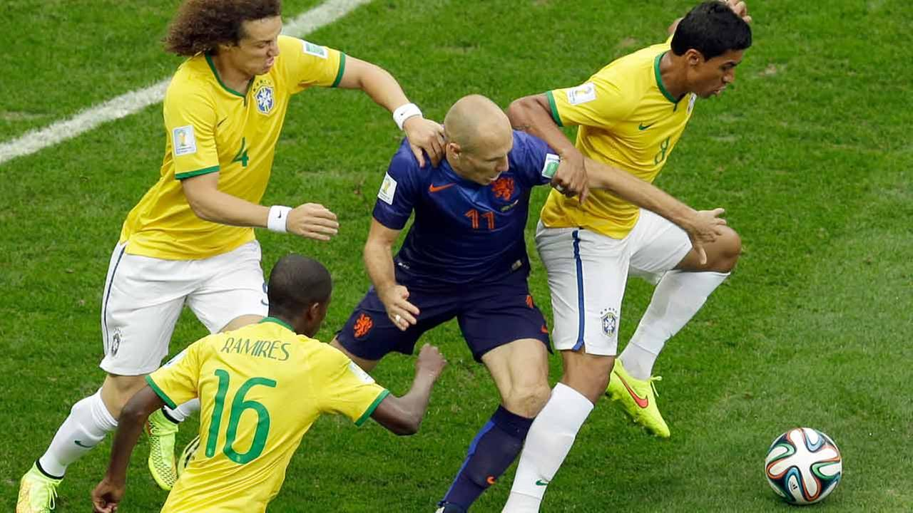 Netherlands Arjen Robben fights for the ball with Brazils Paulinho, and Brazils David Luiz during the World Cup third-place soccer match between Brazil and the Netherlands.