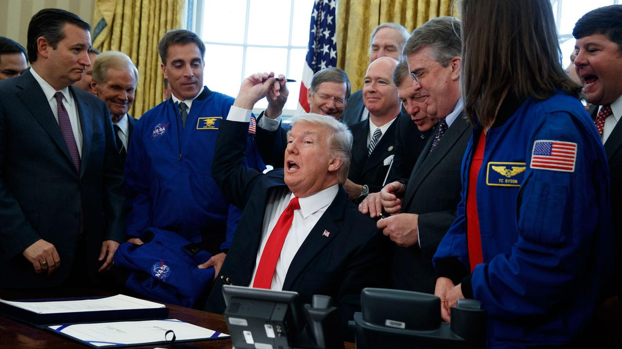 President Donald Trump hands out pens after signing a bill to increase NASAs budget to  $19.5 billion and directs the agency to focus human exploration of deep space and Mars.