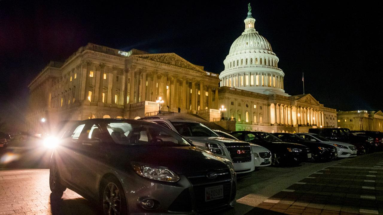Parked cars surround the U.S. Capitol as the lights burn into the evening on the House of Representative side of the U.S., Capitol on Thursday night, March 23, 2017, in Washington.