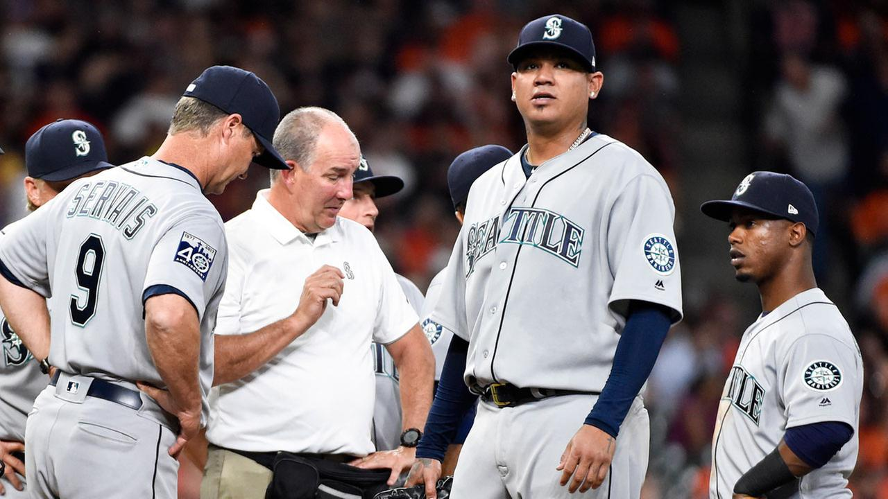 Seattle Mariners starting pitcher Felix Hernandez, second from right, is checked out by manager Scott Servais (9) and a trainer in the fourth inning of the game.AP Photo/Eric Christian Smith