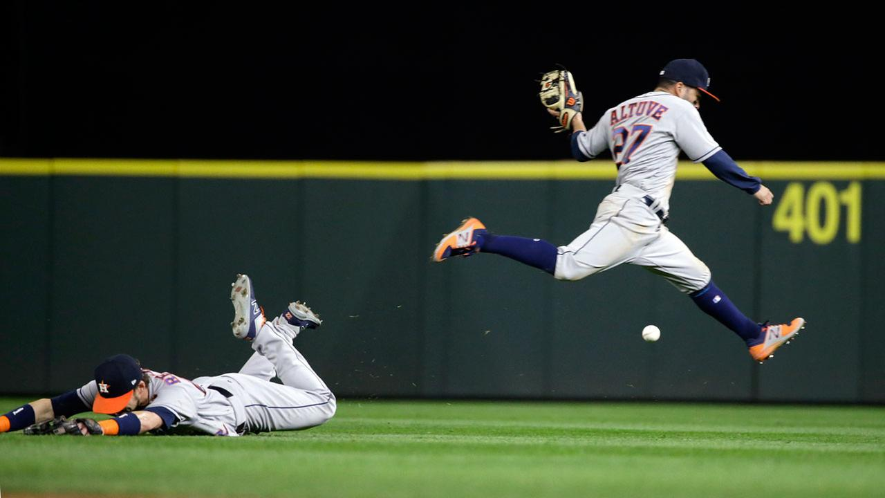 Astros right fielder Josh Reddick, left, misses the ball on a dive as second baseman Jose Altuve leaps past on a single by Seattle Mariners Mike Zunino in the sixth inning.AP Photo/Elaine Thompson