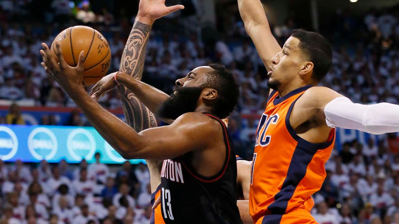 Houston Rockets guard James Harden, center, goes up for a shot between Oklahoma City Thunder center Steven Adams, rear, and forward Andre Roberson, right. (AP Photo/Sue Ogrocki)