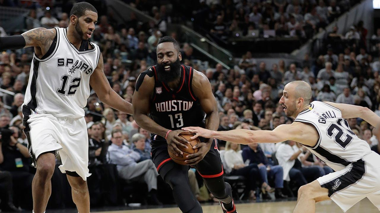 Houston Rockets guard James Harden (13) drives between San Antonio Spurs forward LaMarcus Aldridge (12) and guard Manu Ginobili (20)